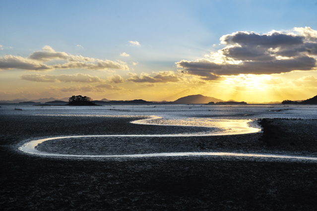 At sunset, a ray of sunshine lights up the vast expanse of the mudflats