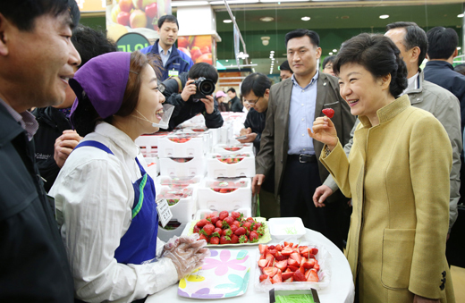President Park Geun-hye tries a strawberry at a free sample stand during the market tour on March 13 (photo: Gonggam Korea).
