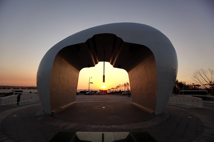 The bell of the Noeuljong sculpture helps frame the sunset's glow.