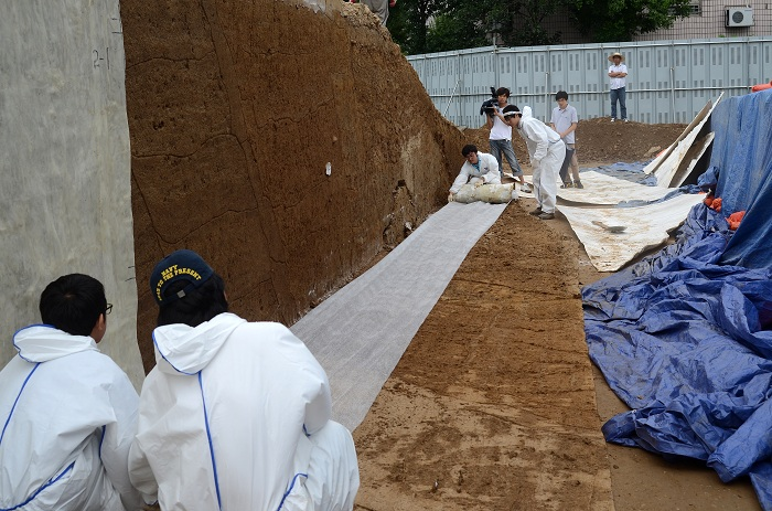 Researchers conduct on-site tests to determine the size of the <i>Pungnaptoseong</i> earthen fortress.