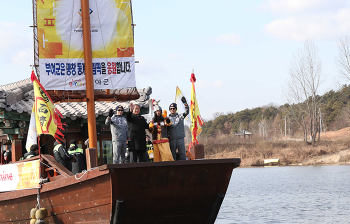 Dressed as a Baekje warrior, a torch bearer waves to the crowd after boarding a traditional yellow sailboat, in Buyeo, Chungcheongnam-do Province, on Dec. 5.
