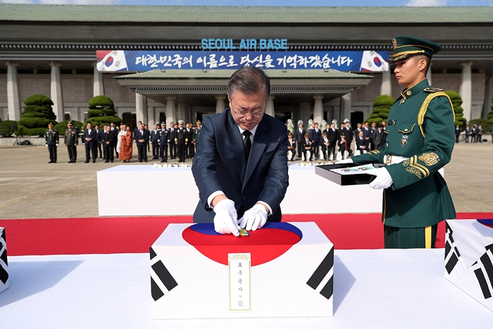 President Moon Jae-in confers a war medal on the soldier remains that returned home 68 years after the Korean War at a commemorative ceremony held at Seoul Airport on Oct. 1.