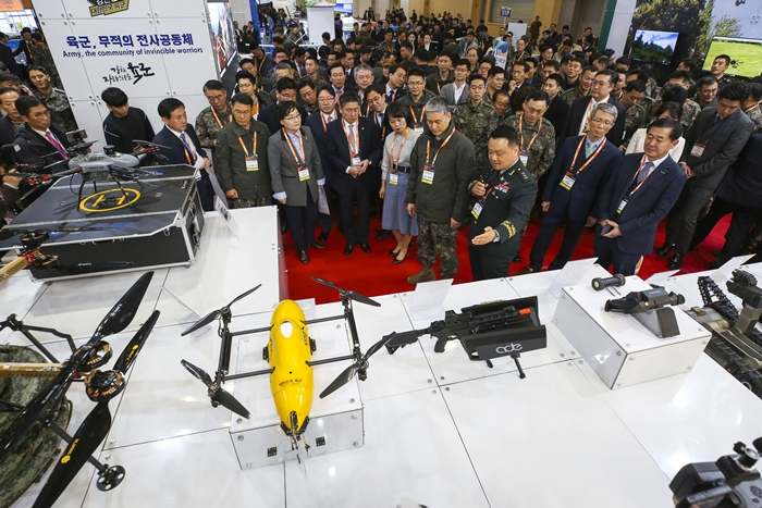 Participants at the Drone Show Korea 2019's opening ceremony on Jan. 24 look at various drones on display at the booth of the Republic of Korea Army. (BEXCO)