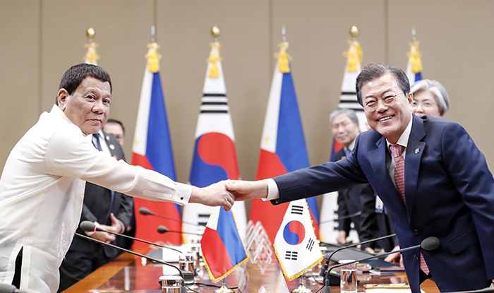 "President Moon Jae-in (second from right) on June 4, 2018, shakes hands with Philippine President Rodrigo Duterte in their summit in Seoul. Both leaders agreed to designate 2019 as the ""Year of Mutual Exchanges between Korea and the Philippines."" (Cheong Wa Dae)"