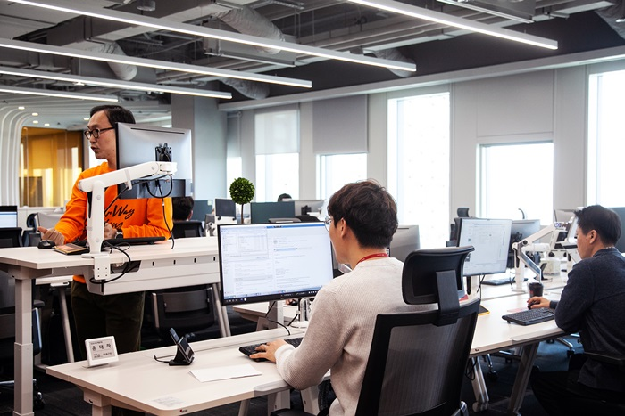 Employees in a 5G smart office can bring up saved data on their desktop monitors by connecting their smartphones to docking pads installed in each desk.