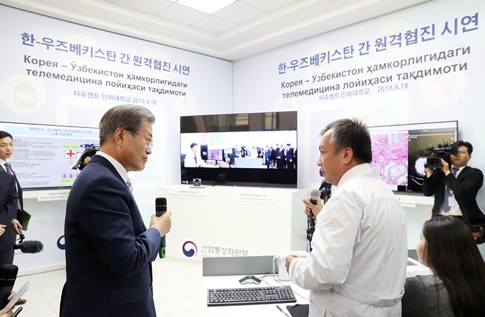 President Moon Jae-in (left) on April 19 listens to an explanation about joint telemedicine between Korean and Uzbek medical teams at Inha University's campus in Tashkent, Uzbekistan. Inha University-Tashkent (IUT) opened in 2014 to allow the Uzbek government to acquire Korea's human resource development system based on information and communications technology. Inha's main campus in Incheon is also financing IUT's establishment advisory and academic management. (Cheong Wa Dae)