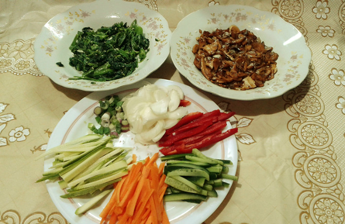 Clockwise from left is blanched spinach with garlic, sesame oil and sesame seeds in the top-left plate; cooked mushrooms in the top-right plate, and carrots, zucchini, cucumber, bell pepper, and white and green onions in the bottom plate.