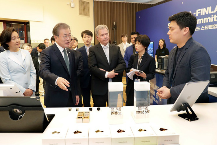 President Moon Jae-in (second from left), accompanied by Finnish President Sauli Niinisto, on June 11 speaks to a representative of a startup at the Korea-Finland Startup Showcase in Helsinki.