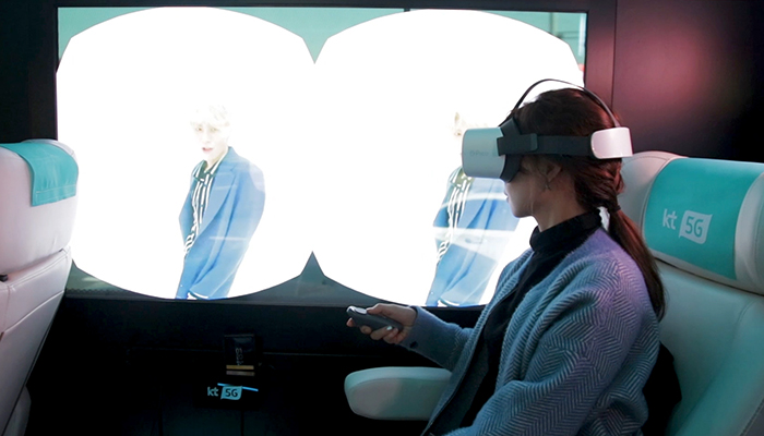 A passenger on a test ride of KT's 5G bus tries a virtual reality (VR) head-mounted display (HMD).