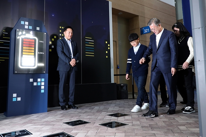 President Moon Jae-in on Feb. 13 visited the Busan Exhibition and Convention Center (BEXCO) to see a presentation on the Busan Smart City Innovative Strategy. He is seen here trying a high-tech floor designed by the Korean company HNJ that transforms kinetic energy into electricity when users step on the tiles with footprints.
