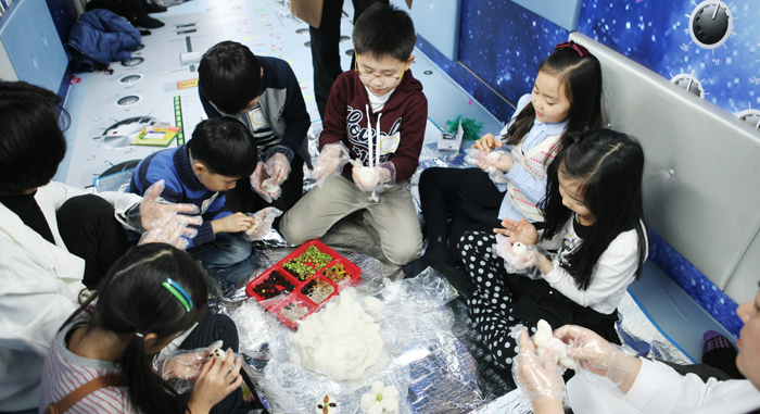 Children make tteok (rice cake) as part of a cultural arts program in the Moving Arts Bus (photo courtesy of MCST).
