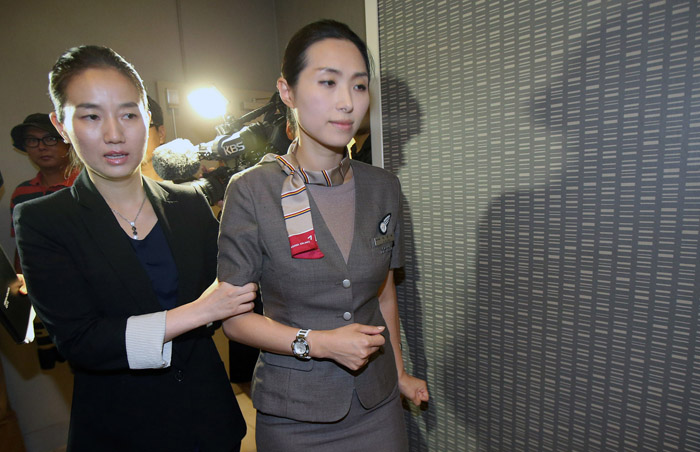 Cabin manager Lee Yun-hye (right) who was aboard the doomed Asiana flight is helped to make her way to a press conference held at Holiday Inn Civic Hotel, San Francisco on July 7 (photo courtesy of Yonhap News).