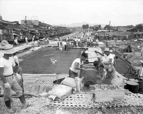 Workers bury Cheonggyecheon under pavement (photo courtesy of Seoul Museum of History).
