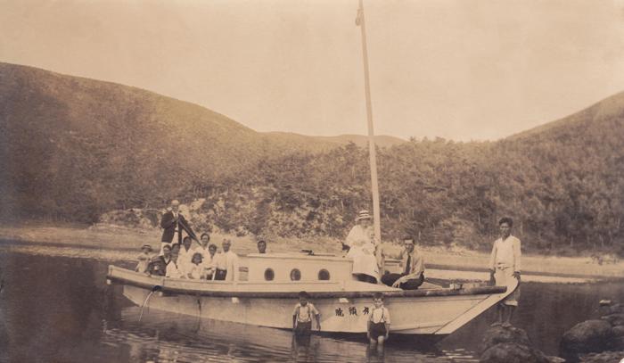 Rev. James Nobel Mackenzie (far left) holds a paddle on a yacht. (photo courtesy of the KCC, Australia)