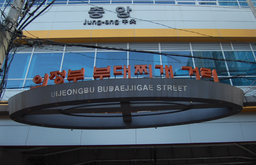 The arch over the entrance to the budae jjigae street doesn't hide the dish's humble origins.