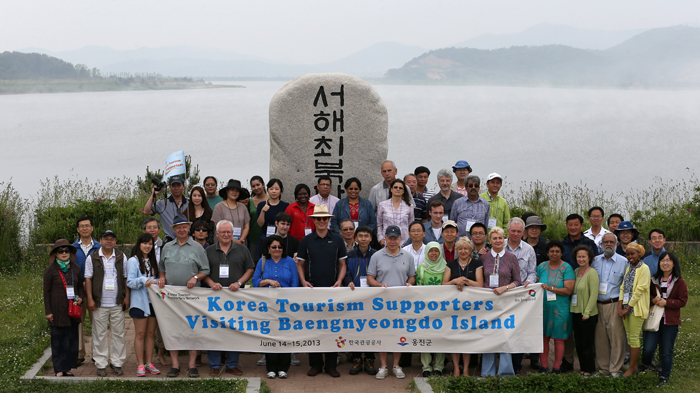 The travel group poses for a photo at the memorial site (photo: Jeon Han).