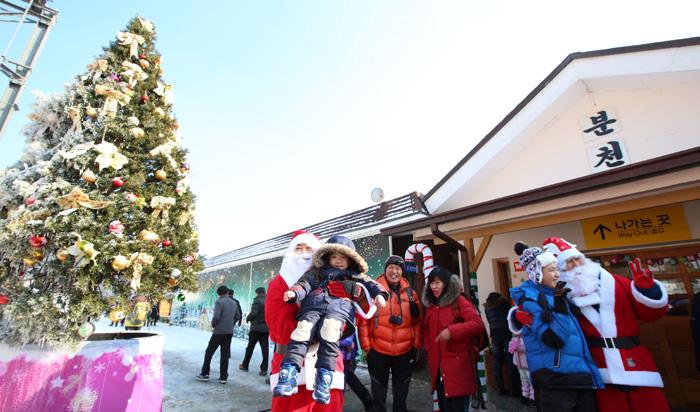 어린이 관광객들이 분천역 산타마을에서 반갑게 맞이하는 산타할아버지와 함께 사진을 찍으며 추억을 남기고 있다.