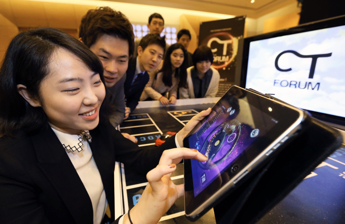 "Visitors try a ""Drive in Theater"" car remote control system based on smartphone technology outside the venue of the CT Forum at COEX on April 16 (photo: Jeon Han)."