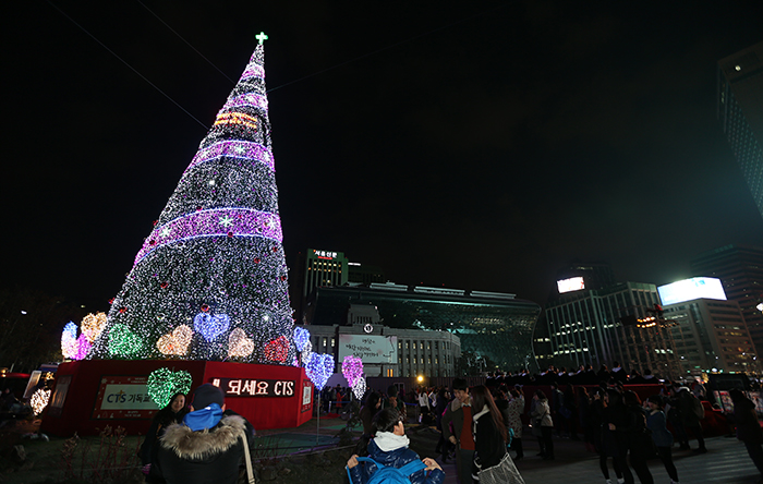 On November 30, citizens collect holiday memories at the giant Christmas tree in the square in front of Seoul City Hall, taking pictures of loved ones and themselves against the festive backdrop. (photo: Jeon Han)
