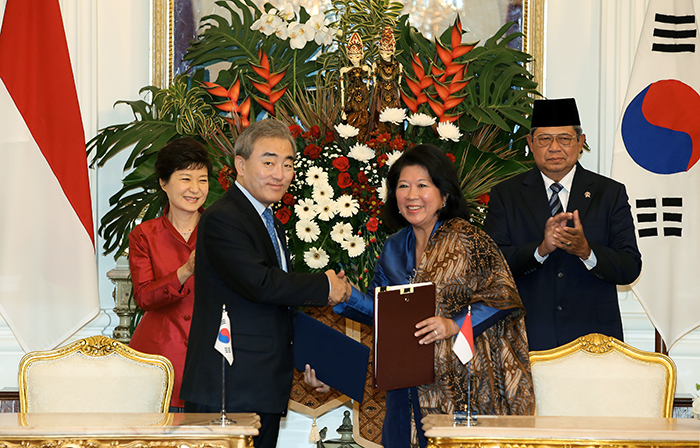 Minister of Culture, Sports & Tourism Yoo Jinryong and Indonesian Minister of Tourism and Creative Economy Mari Elka Pangestu shake hands after signing an MOU on creative-industry cooperation between Korea and Indonesia. President Park Geun-hye (left, back row) and Indonesian President Susilo Bambang Yudhoyono (right, back row) are present during the MOU signing ceremony in Jakarta, Indonesia, on October 12. (Photo: Cheong Wa Dae)