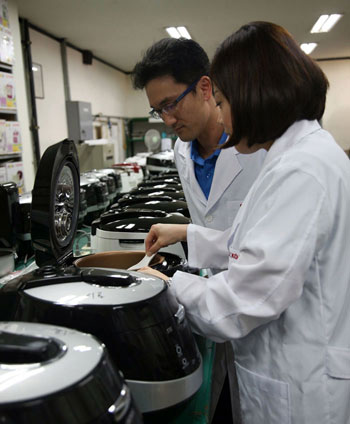 Researchers at Cuckoo Electronics examine the cooked rice from a Cuckoo rice cooker.