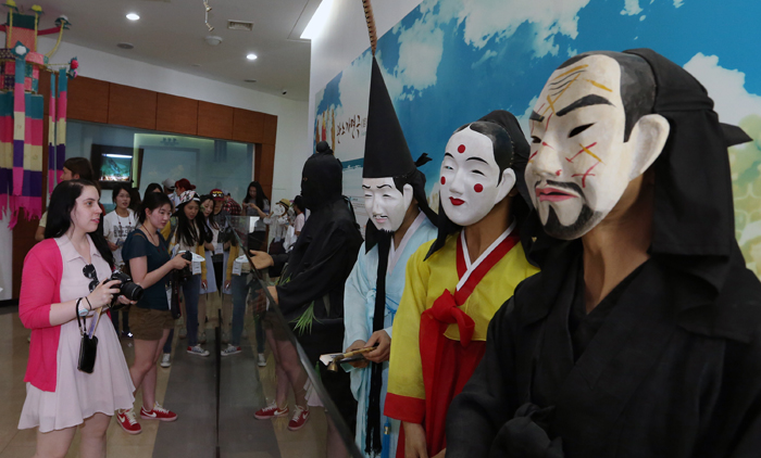 Visitors appreciate <i>tal</i>, masks used for traditional performances, part of the Gangneung Danoje festival, at the Gangneung Dano Culture Center in Gangneung, Gangwon-do, on June 1. (photo: Jeon Han)