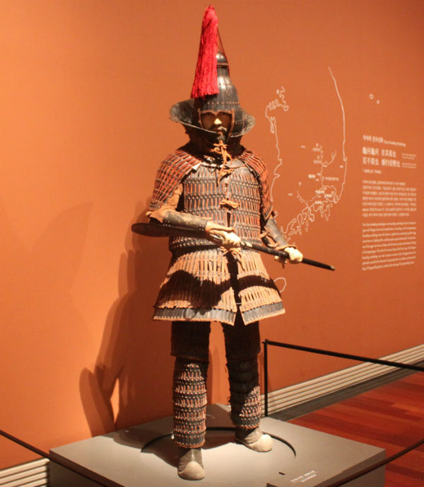A statue of a warrior wearing steel scale armor and a helmet inside the new Gaya Exibition Hall (photo courtesy of the National Musem of Korea)