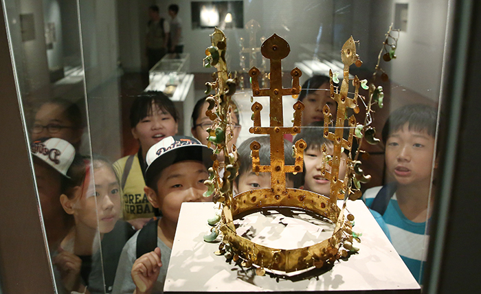 Young museum goers admire a golden crown from the Silla Kingdom, a relic discovered at the Geumgwanchong Tomb in Gyeongju, the then capital of the ancient kingdom, at the National Museum of Korea. (photo: Jeon Han)
