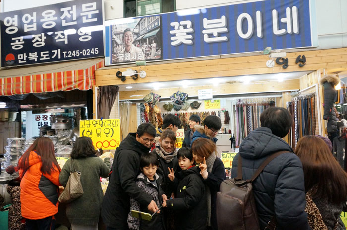 People take selfies in front of <i>Kkobbunine</i>, the shop which the character Deoksu runs in the movie 'Ode to My Father.' Much of the movie was filmed in and around Gukje Market in Busan.
