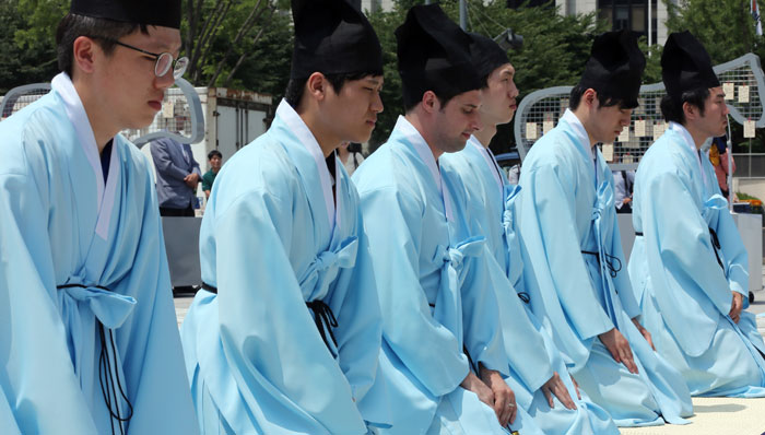 Expatriates and members of multicultural families learn the ancestral ritual by taking part in a demonstration event while wearing the attire of Joseon-era Confucian scholars. (photo: Yonhap News)