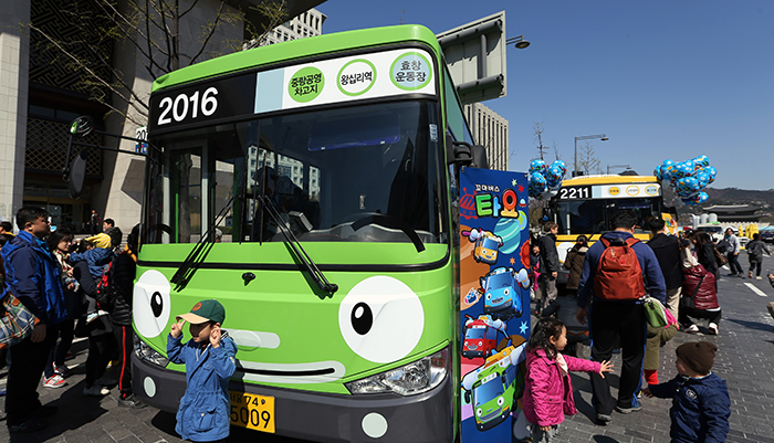 """Children pose in front of Rogi, the green bus, one of the four main characters from """"Tayo the Little Bus,"""" at Gwanghwamun Square in central Seoul on April 6. (photo: Jeon Han)"""