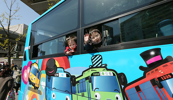 Children wave out the windows of Tayo on April 6 at Gwanghwamun Square in central Seoul. (photo: Jeon Han)