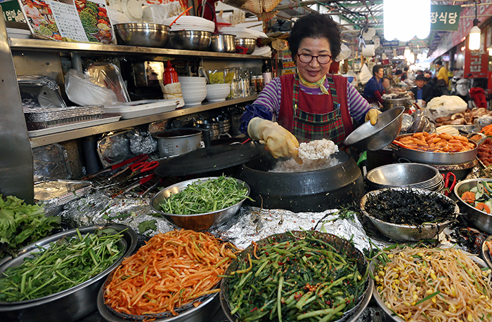 Seo Geum-yeon prepares a bowl of <i>bibimbap</i>, mixed rice with various ingredients, as she scoops rice from an iron pot into a large bowl on April 10. She has been selling <i>bibimbap</i> for almost 20 years in the food alleys of Gwangjang Market in Jongno-gu District in central Seoul. (photo: Jeon Han)