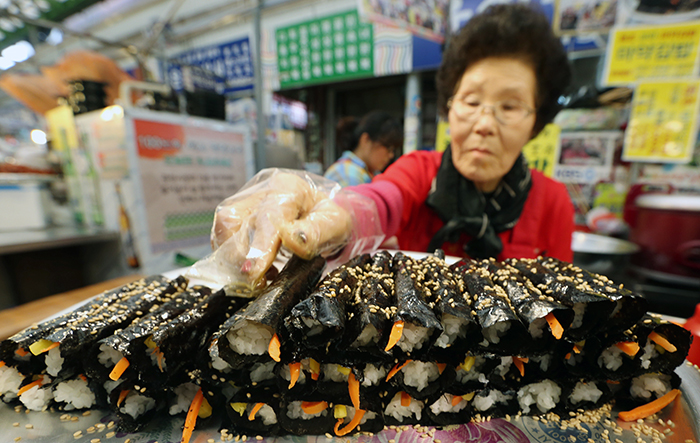 "Dubbed ""narcotic"" <i>gimbap</i> for its addictive taste, <i>mayak gimbap</i> is known as one of the most iconic foods of Gwangjang Market. It is made with cooked rice, seaweed, vegetables, sesame oil and sesame seeds. (photo: Jeon Han)"