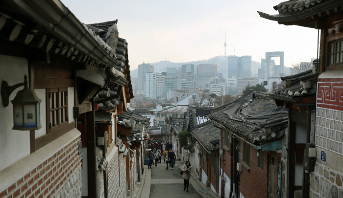 The Bukchon Hanok Village, a neighborhood of traditional Hanok residences in Jongno-gu, Seoul, creates a contrast between tradition and modernity, as it blends with the surrounding high-rises. The stark contrast attracts tourists not only from home, but from abroad, too.