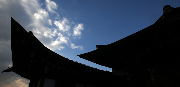 The cloudless clear sky is spread above and between Hanok roofs.
