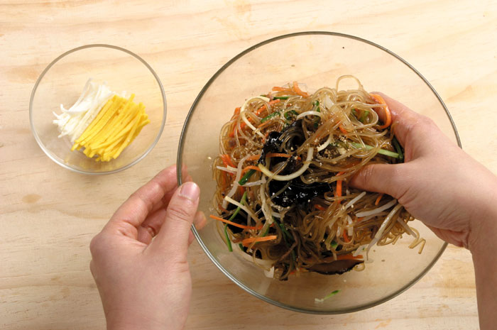 Pork, spinach, oyster mushrooms and other ingredients may be added to <i>japchae</i>. It's served with the noodles mixed with the other ingredients and topped with yellow and white egg strips.