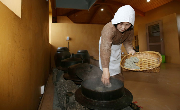 Kang Kyoung-soon, a master brewer of <i>omegisul</i>, places some <i>omegitteok</i>, traditional cakes made from millet into the boiling water. This is part of brewing <i>omegisul</i>, a traditional grain-based alcoholic beverage from Jeju Island.