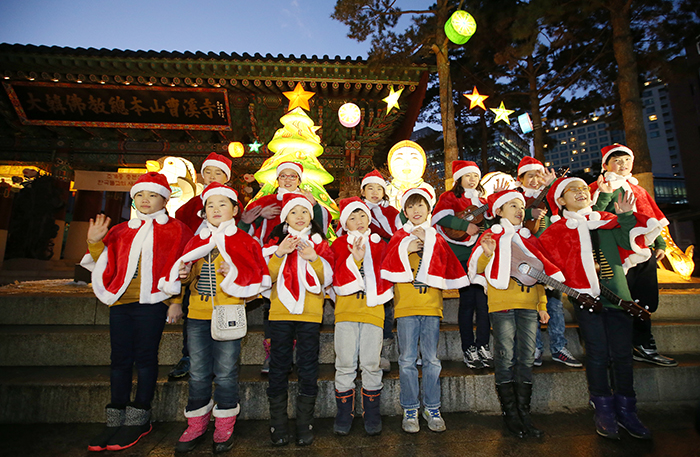 Members of a children's choir call out, 'Merry Christmas,' and wave to the audience in front of a lit Christmas tree at the main gate to Jogyesa Temple on December 17.