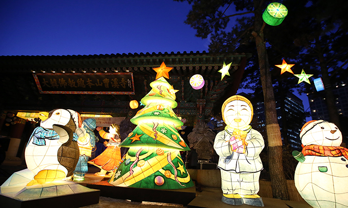 A Christmas tree is switched on in front of the Iljumon, the main gate to Jogyesa Temple, as a symbol of unified religions, on December 17. Next to the tree are large lanterns in different shapes, including a smiling child monk, a snowman and a penguin.
