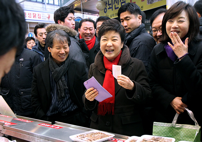 Then President-elect Park Geun-hye (center) visits Junggok Market on February 8, where she buys street food from a vendor (photo courtesy of President Park Geun-hye's Flickr page).