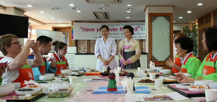 "Foreign participants listen to Yoon Sook-ja (center right), director of the Institute of Traditional Korean Food, explaining Korean royal court cuisine ""neobiani"" during a Korean food experience program titled Have you ever K-food on May 24 (photo: Jeon Han)."