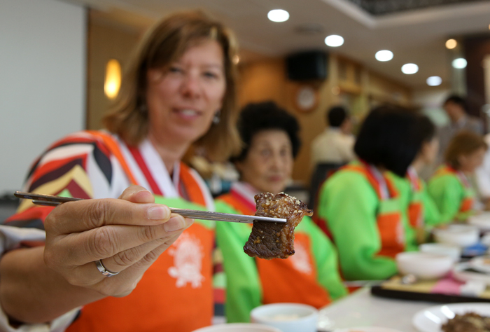 Betty Williams, an American participant uses her chopsticks on a piece of neobiani she made during the cooking class on May 24 (photo: Jeon Han).