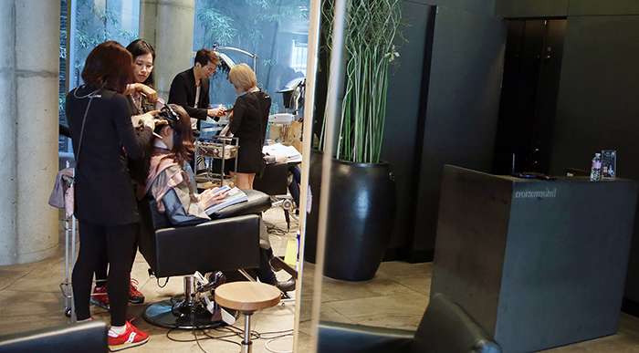 Staff at Avenue Juno concentrate on a customer's hair style. (photo: Jeon Han)