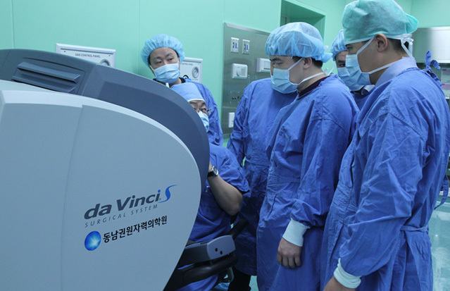 Visitors from Kazakhstan closely watch a surgery robot operating at Dongnam Institute of Radiological and Medical Sciences (photo: Yonhap News).