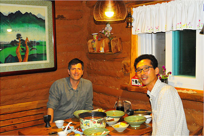 Farm owner Kim Young-mee excels at cooking and photography. Here WWOOFer David Kendall enjoys gejjigae (crab stew) and omija wine with her husband Im So-hyeon in their kitchen.