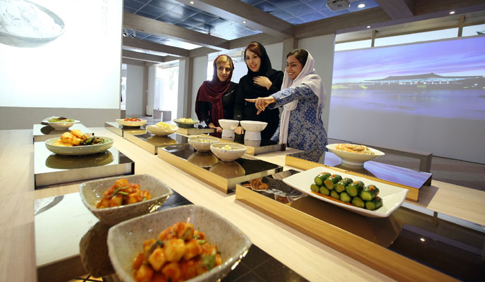 A group of Iranian university students check out the kimchi on display at the K-Culture Exhibit at the Milad Tower in Tehran on May 2. A range of kimchi was on display, including varieties that used tomatoes, onions and pomegranates.