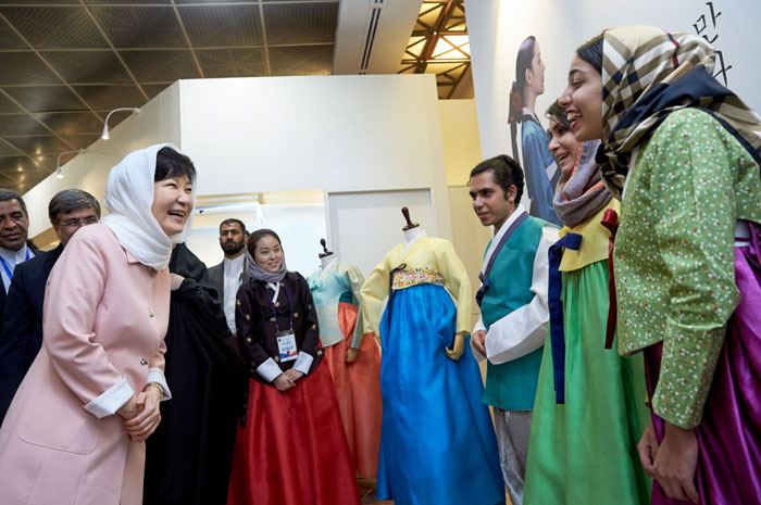President Park Geun-hye (left) talks with Iranian youth who are wearing traditional Korean Hanbok attire at the K-Culture Exhibit in Tehran on May 2.