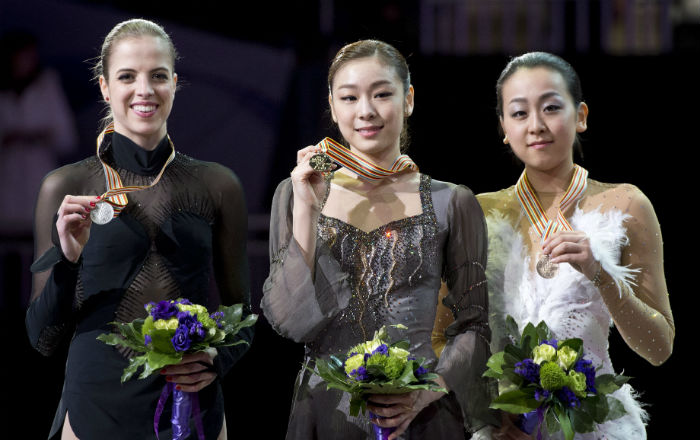 Kim Yu-na (center), Carolina Kostner of Italy, and Mao Asada from Japan pose together on the podium during the medal ceremony for the women's competition at the 2013 World Figure Skating Championships, on Saturday, March 16, in London, Ontario, Canada (photo: Yonhap News).