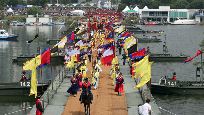The 2017 King Jeongjo Tomb Parade crosses a <i>baedari</i> (배다리), a bridge built on multiple boats that connects the neighborhood of Ichon with Nodeulseom Island in the Hangang River, in central Seoul on Sept. 23.